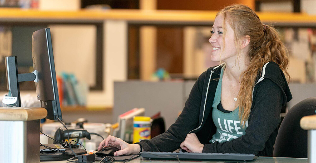 student assistant working at circulation desk