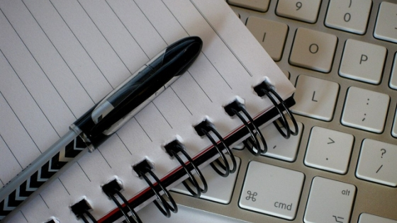 computer keyboard and pen with paper