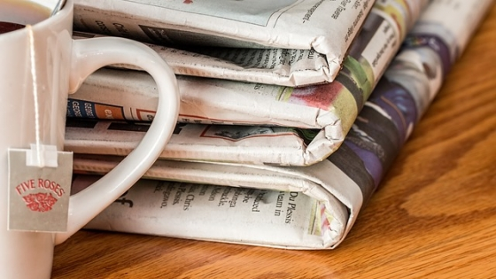 A stack of newspapers and a cup of tea