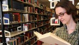 woman reading book by library stacks