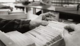 hands looking through sdsu card catalog